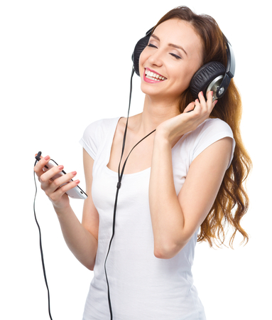 Closeup portrait of lovely young woman enjoying music using headphones, isolated over white Stock Photo - 22484734