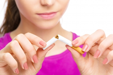 smoking: Young woman is breaking a cigarette, quit smoking concept, isolated over white