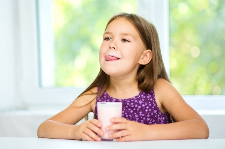 girl licking: Cute little girl is licking her lips while drinking milk