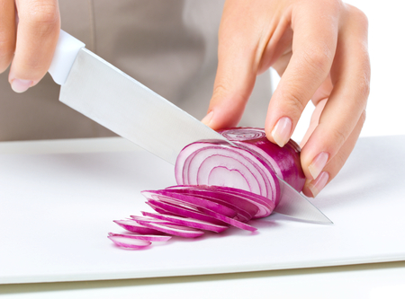 slicing: Cook is chopping onion, closeup shoot, isolated over white
