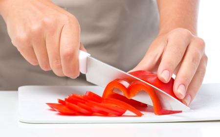 chopping: Cook is chopping bell pepper, closeup shoot, isolated over white
