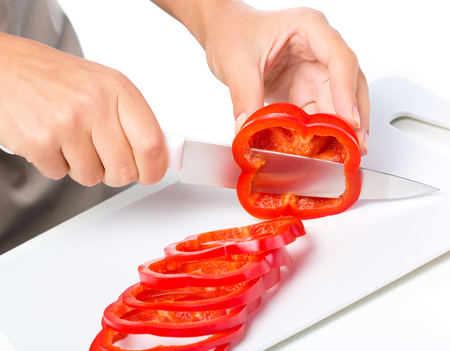 slicing: Cook is chopping bell pepper, closeup shoot, isolated over white