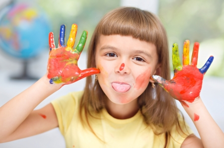 child drawing: Portrait of a cute cheerful girl showing her tongue and hands painted in bright colors Stock Photo