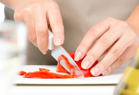 slicing: Cook is chopping bell pepper, closeup shoot