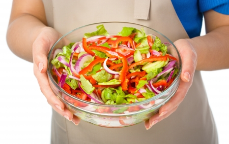 Cook is holding a big bowl with fresh summer salad, closeup shoot, isolated over white photo