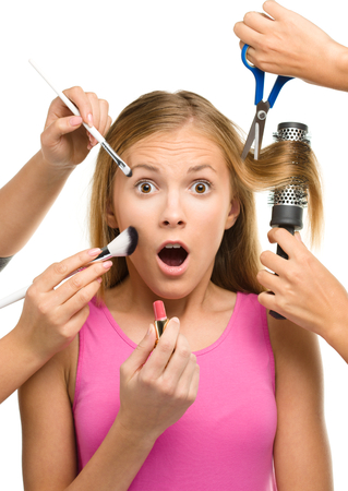 makeover: Makeover process of a young teen girl, few hands are helping to apply makeup and cut hair, isolated over white