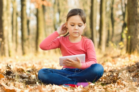 one story: Cute little girl is reading a book outdoors Stock Photo