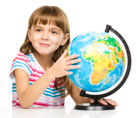 Little girl is examining globe while sitting at table, isolated over white photo