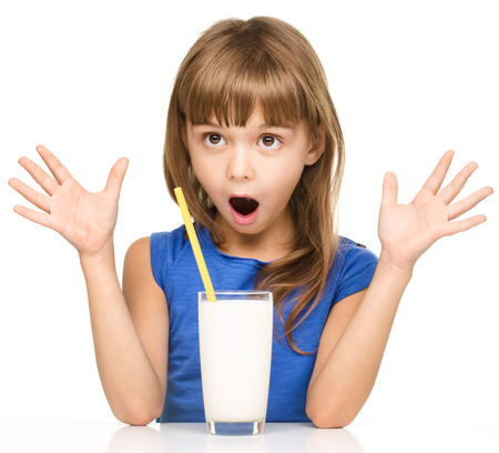 Cute little girl drinks milk using a drinking straw, isolated over white