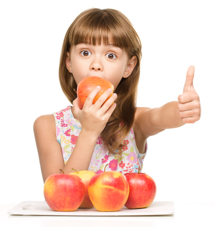 Portrait of a little girl with red apples showing thumb up sign, isolated over white photo