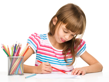 drawing table: Little girl is drawing using color pencils while sitting at table and sticking her tongue out, isolated over white
