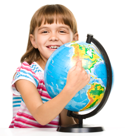 Little girl is pointing at something on globe, isolated over white
