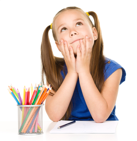 Little girl is daydreaming while sitting at table and drawing with color pencils, isolated over white photo