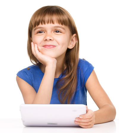 wishful: Wishful thinking young girl is using tablet while sitting at table, isolated over white Stock Photo