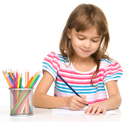 drawing table: Little girl is drawing using color pencils while sitting at table, isolated over white