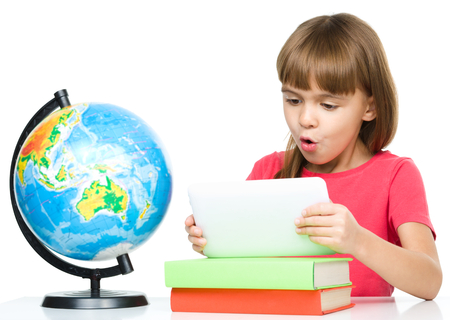 Surprised young girl is using tablet while studying geography, isolated over white Stock Photo