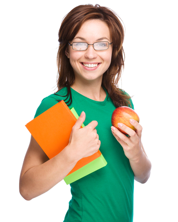 Young student girl is holding exercise book and apple, isolated over white photo