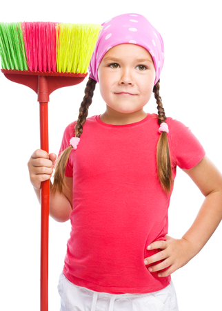 Young girl is dressed as a cleaning maid and holding broom, isolated over white Stock Photo - 24397969