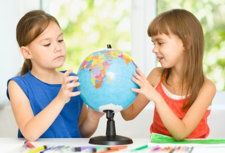 Little girls are examining globe while sitting at table photo