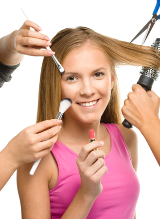 Makeover process of a young teen girl, few hands are helping to apply makeup and cut hair, isolated over white