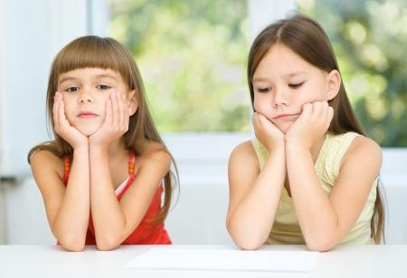 niños tristes: Retrato de dos niñas tristes están sentados en la mesa