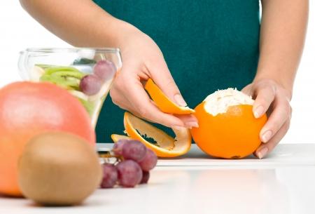 vegs: Cook is peeling orange for fruit dessert, closeup shoot, isolated over white