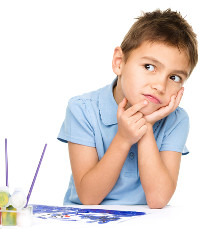 Young is daydreaming while drawing with paints, isolated over white photo
