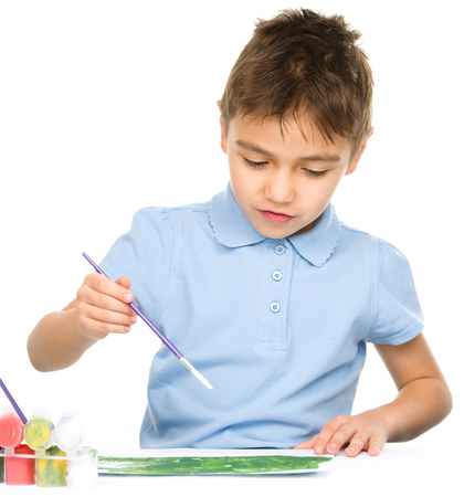 Portrait of a cute boy playing with paints, isolated over white photo