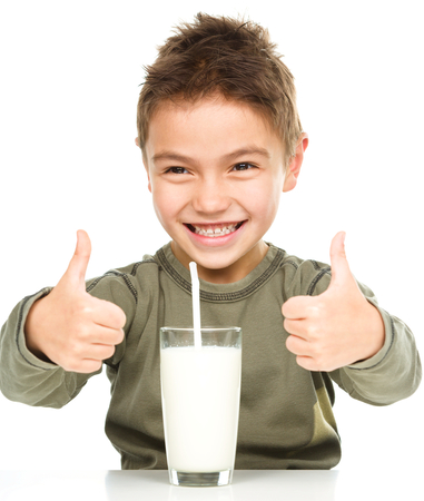 drinking straw: Cute boy with glass of milk is showing thumb up sign using both hands, isolated over white Stock Photo
