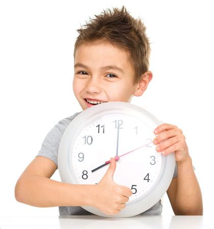 Boy is holding big clock and showing thumb up sign, isolated over white photo