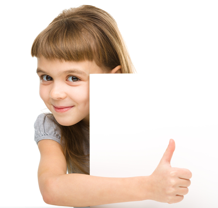 Little girl is looking out from the blank banner and showing thumb up sign, isolated over white photo