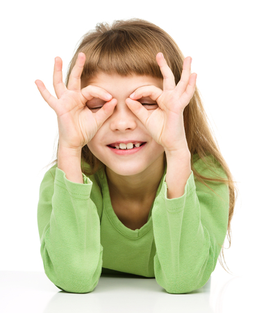 Happy little girl is showing glasses gesture, isolated over white photo