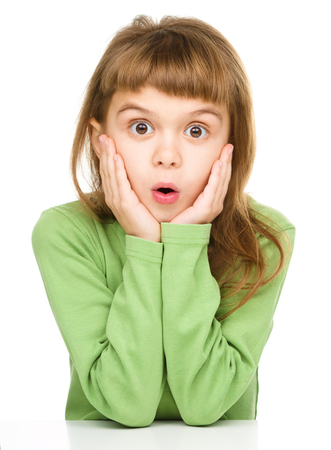 Little girl is holding her face in astonishment, isolated over white photo