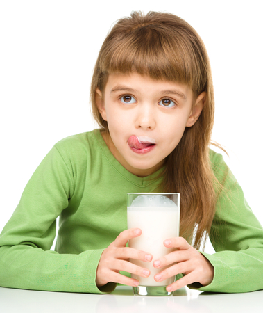 licking in isolated: Cute little girl showing milk moustache and licking her lips, isolated over white Stock Photo