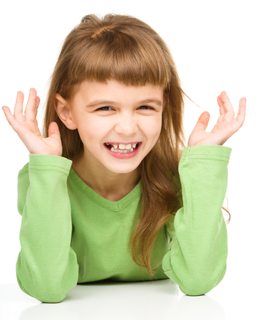 exhilarated: Portrait of a happy little girl laughing, isolated over white