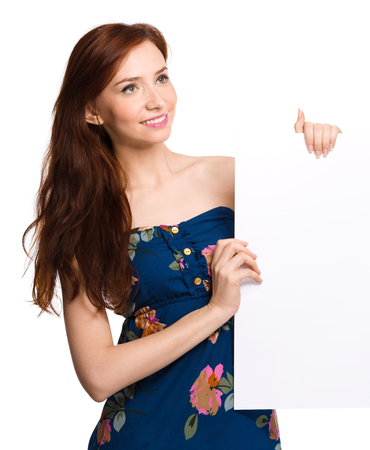 Young woman is holding blank banner, isolated over white photo