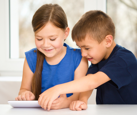 Children are using tablet while sitting at table, isolated over white photo