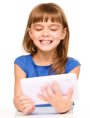 exhilarated: Young cheerful girl is using tablet while sitting at table, isolated over white
