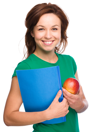 Young skinny student girl is holding exercise book and apple, isolated over white photo
