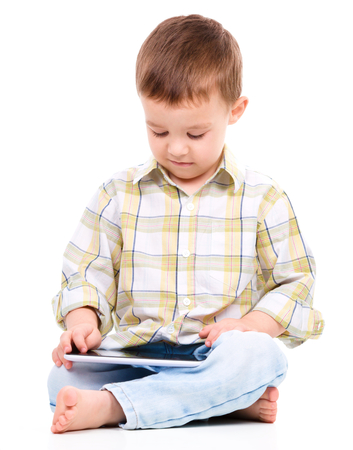 Young boy is using tablet while sitting on floor, isolated over white photo
