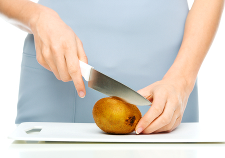 chopping: Cook is chopping kiwi fruit, closeup shoot, isolated over white