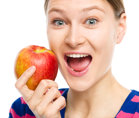 exhilarated: Young happy girl is holding red apple, isolated over white