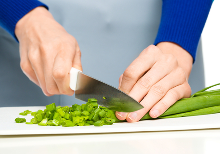cutting vegetables: Cook is chopping green onion, closeup shoot, isolated over white