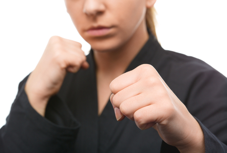 self defense: Young woman in black kimono is ready to fight, isolated over white