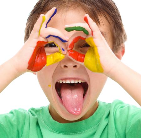 schoolchild: Portret van een leuke vrolijke jongen die zijn handen geschilderd in felle kleuren en steken tong uit, geïsoleerde over wit Stockfoto