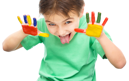 fingerpaint: Portrait of a cute cheerful boy showing his hands painted in bright colors and sticking tongue out, isolated over white