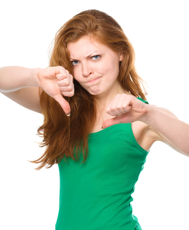 Young woman is showing thumb down gesture using both hands and funny grimace on her face, isolated over white photo
