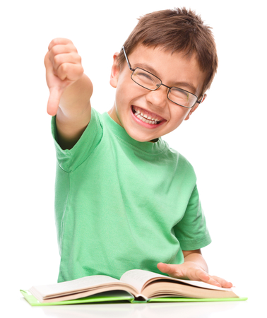 Cute little girl is reading a book and showing thumb down sign, isolated over white photo