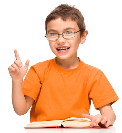 boy book: Cute little boy is reading a book while wearing glasses and explaining something gesturing with hands, isolated over white