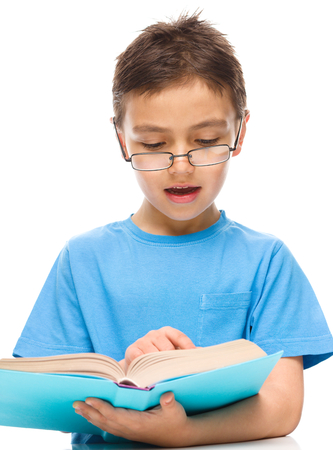 boy book: Cute little boy is reading a book while wearing glasses, isolated over white Stock Photo